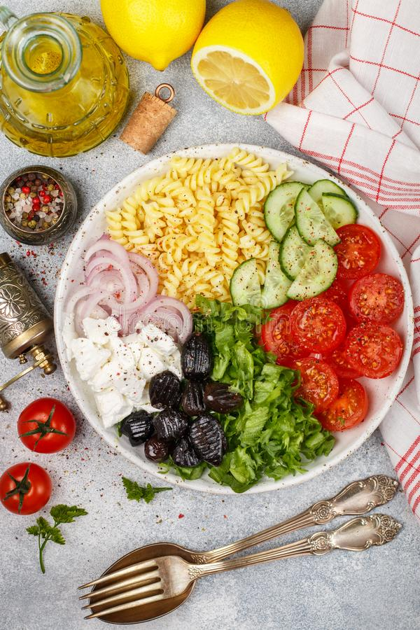 Greek salad with fusilli paste, lettuce, tomatoes, cucumber, feta cheese, red onions and black olives. Dressed with olive oil. A delicious Mediterranean royalty free stock photography
