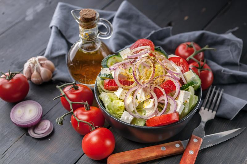 Greek salad with olive oil and spices. Onion, garlic, fork and spoon, gray napkin on a dark wooden table. Horizontal shot stock image