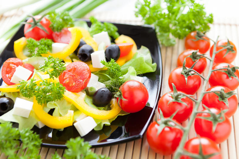 Greek salad and a sprig of cherry tomatoes. Close up stock photos