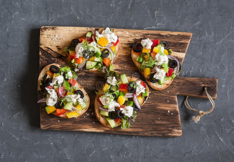 Greek salad style bruschetta on a wooden cutting board, on dark background, top view. stock photos