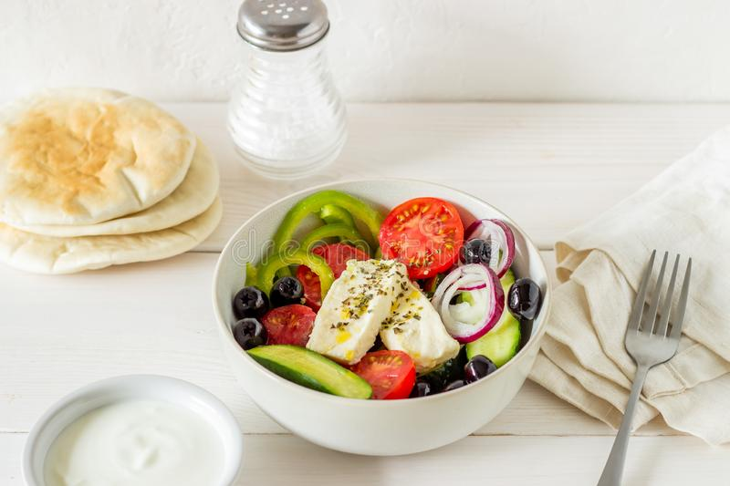 Greek salad on a white wooden background. Tomatoes, peppers, olives, cheese, onions. Healthy eating. Diet. Vegetarian food. Greek salad on a white wooden stock photo