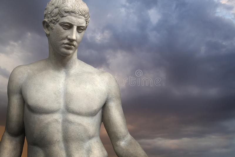 Greek Sculpture. Young Adonis bronze statue with blue sky background stock photo