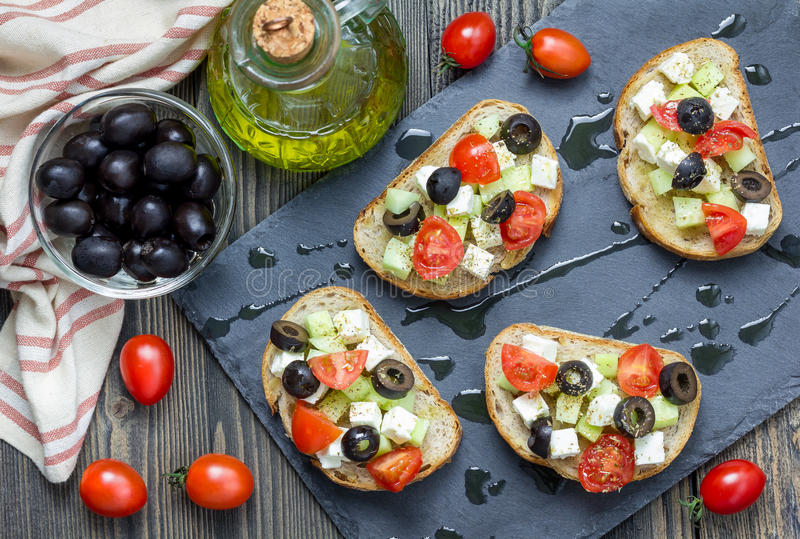 Greek style crostini with feta cheese, tomatoes, cucumber, olives and herbs stock image