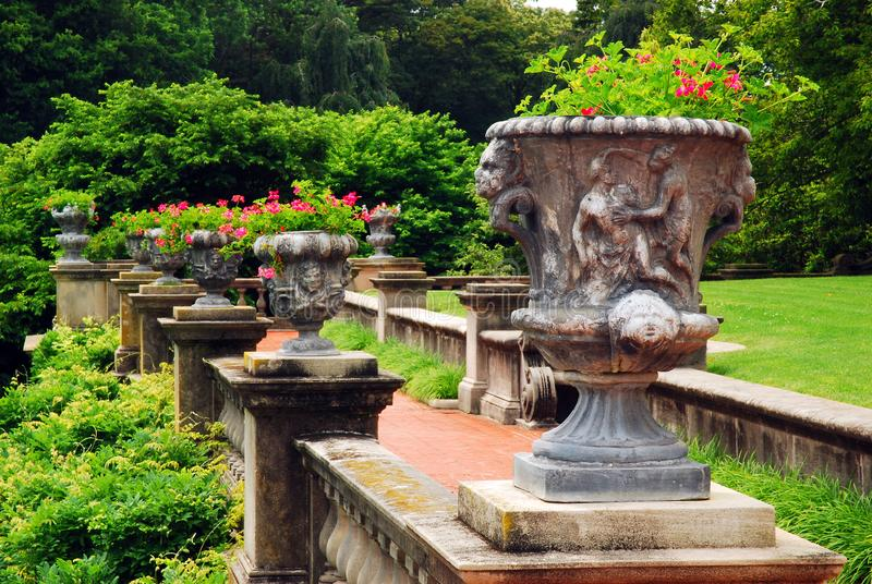 Greek style urns decorate a terrace in the summer. At Old Westbury Gardens stock image