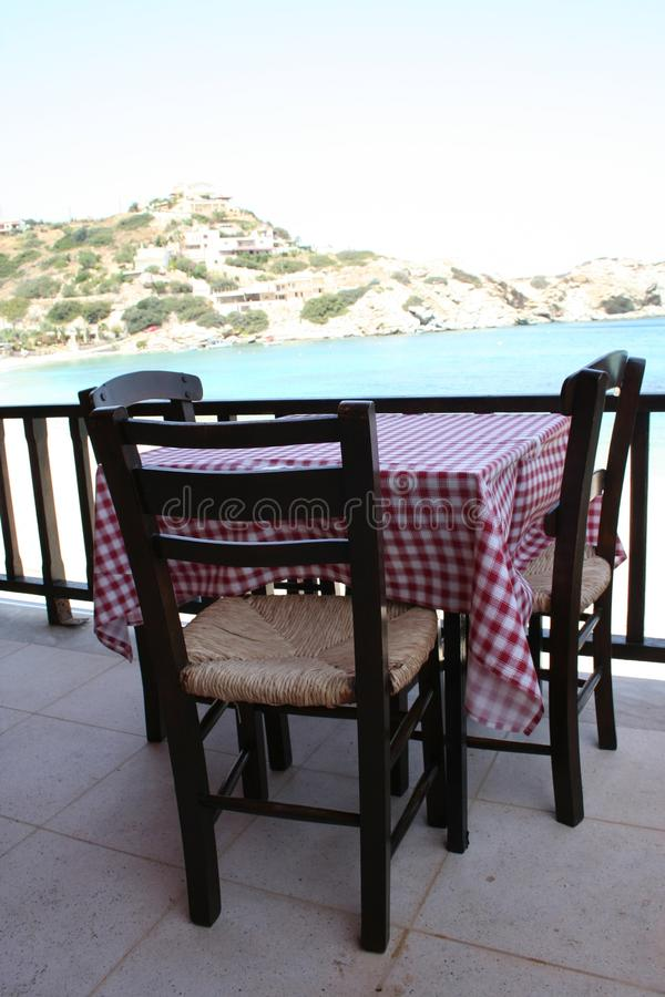 Greek Tavern. Restaurant table with read and white table cloth and wooden chairs. Crete, Island in Greece royalty free stock photo