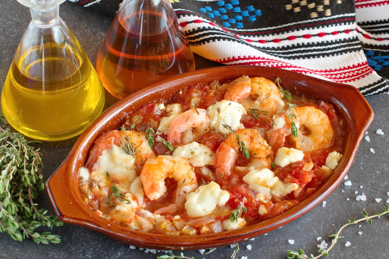 Oven backed prawns with feta, tomato, paprika, thyme in a traditional ceramic form on a abstract background. Healthy eating concep royalty free stock images