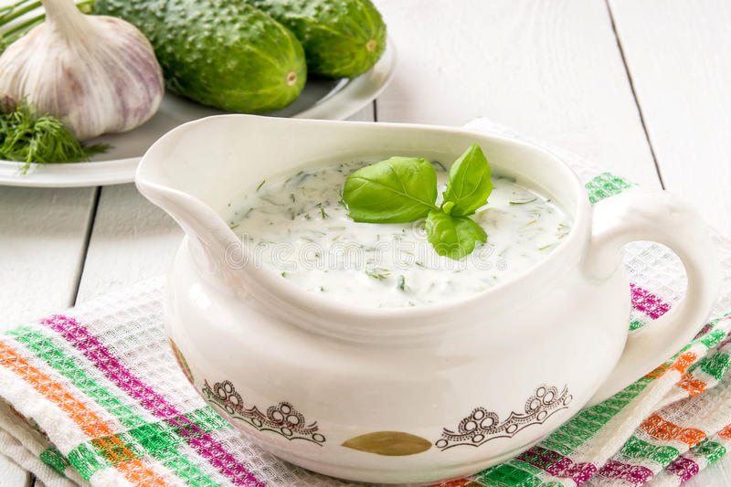 Greek Tzatziki sauce. With yogurt, ingredients: cucumber, garlic and dill on a plate on white wooden table. Selective focus stock photo