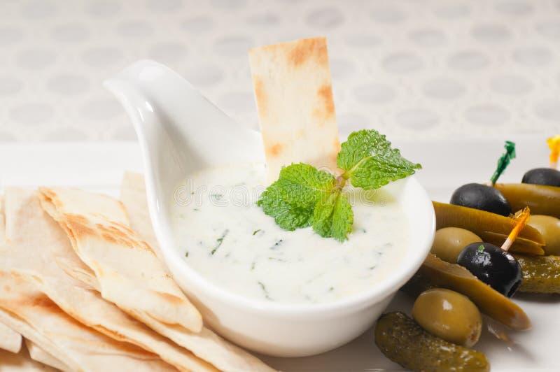 Greek Tzatziki yogurt dip and pita bread. Fresh Greek Tzatziki yogurt dip and pita bread and pickels royalty free stock photo