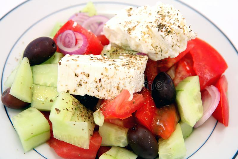 Greek village salad. Traditional Greek village salad with tomato, cucumber, olives, onion, feta cheese and sprinkled with oregano stock images