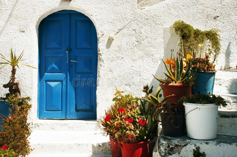 Greek welcome on Santorini. The entrance to a traditional greek house with blue gates and a whitewashed wall, and colourful plants to welcome visitors royalty free stock images