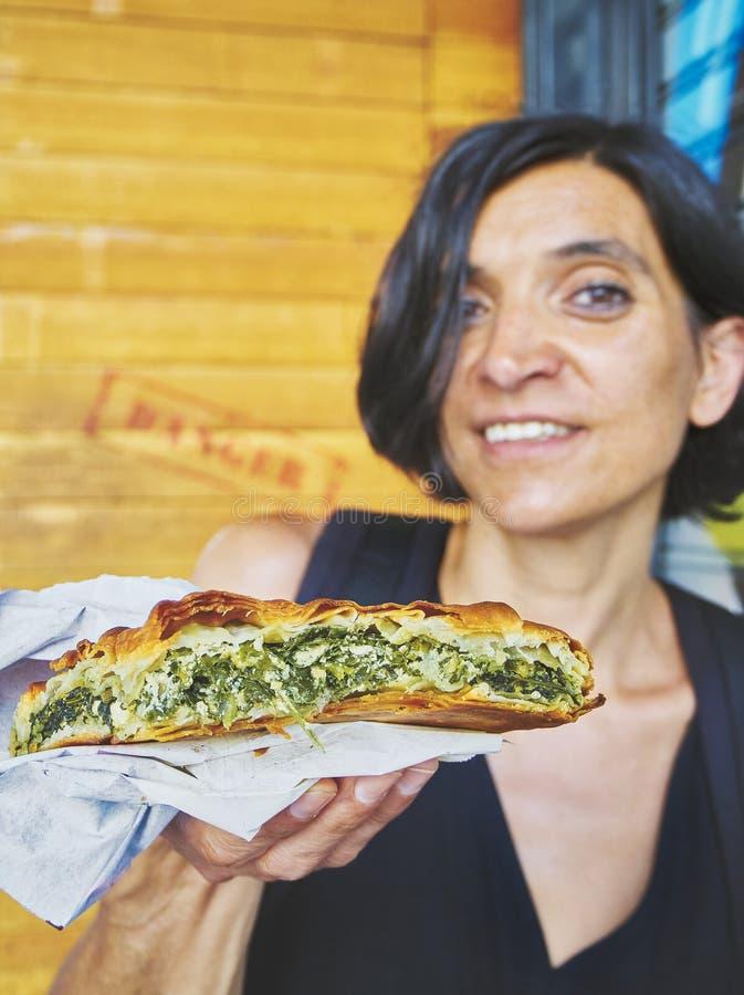 Free Greek Woman Eating A Traditional Spanakotiropita, Spinach And Feta Pie. Royalty Free Stock Photo - 122793715