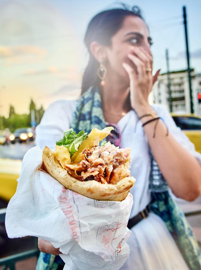 Greek woman eating a Gyros in a street of Athens. Athens, Greece - June 29, 2018. Greek woman eating a traditional Gyros, set on Pita bread, typical of greek stock images