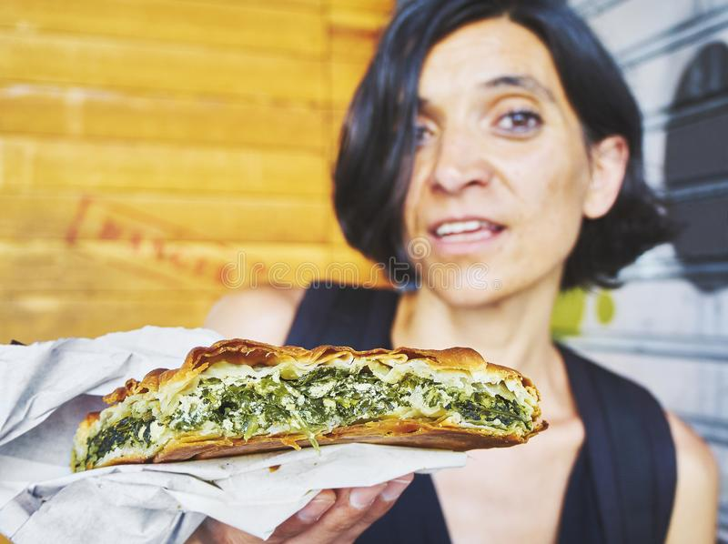 Greek woman eating a traditional Spanakotiropita, Spinach and Feta pie. stock photo