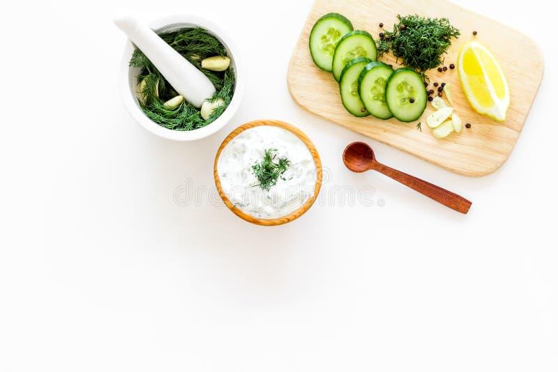 Greek yogurt as salad dressing. Bowl with yogurt, greenery, cucumber, oranges on cutting board on white kitchen desk top royalty free stock images