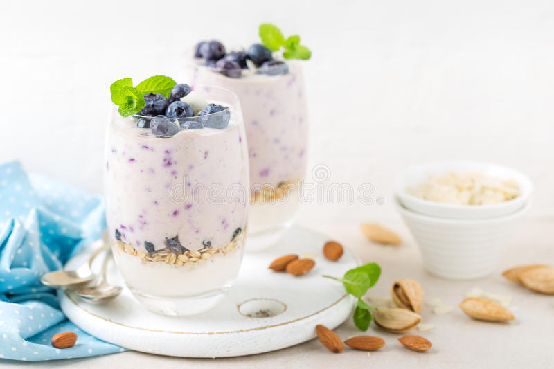 Greek yogurt or blueberry parfait with fresh berries and almond nuts on white background. Healthy eating stock photography