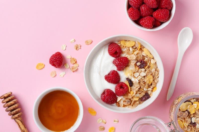 Greek yogurt in bowl with raspberries, honey and muesli on pink table top view. Healthy diet breakfast stock photo