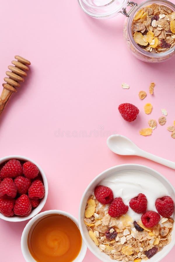 Greek yogurt in bowl with raspberries, honey and muesli on pink table top view. Healthy diet breakfast stock image