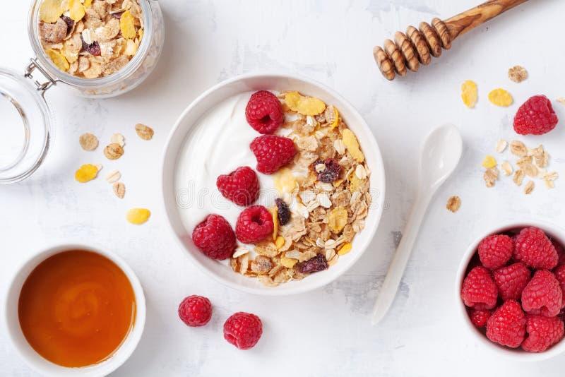 Greek yogurt in bowl with raspberries, honey and muesli on white stone table top view. Healthy diet breakfast royalty free stock image