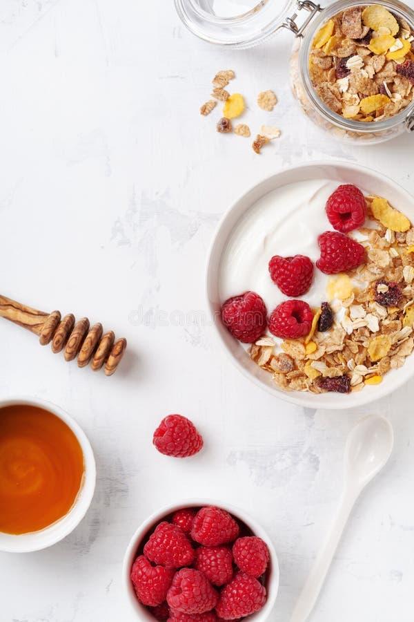 Greek yogurt in bowl with raspberries, honey and muesli on white table top view.  stock photos