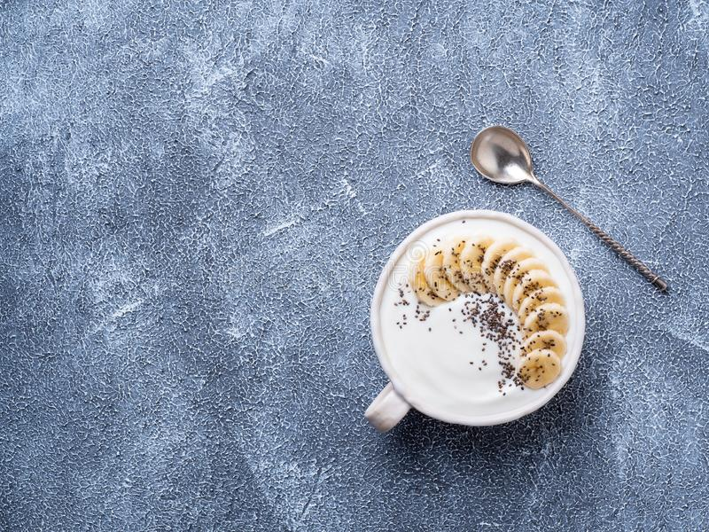 Greek yogurt with chia seeds and banana in white bowl on grey bl. Ue concrete stone table, top view, copy space stock photos
