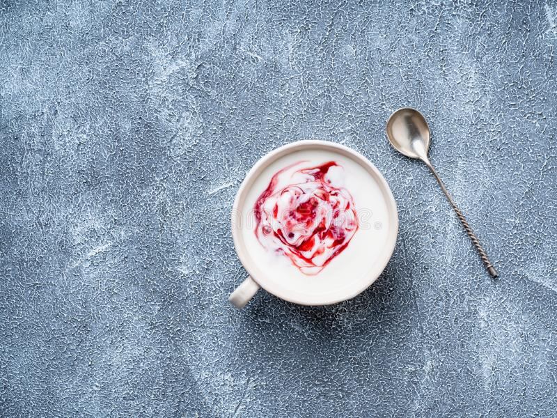 Greek yogurt with jam in white bowl on grey blue concrete stone. Table, top view, copy space royalty free stock photo