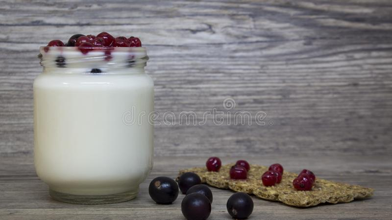 Greek yogurt, milk, smoothies, blueberries and currants in a glass jar on a wooden table, detox, diet royalty free stock images