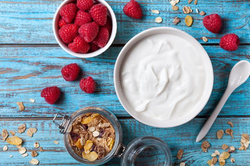 Greek yogurt with raspberries and muesli on blue wooden table top view stock photography