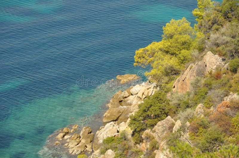 Greeks, sea coast, waves at sea. The rock hangs over the sea. Bushes royalty free stock photos