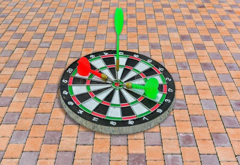 Green Dart hitting on center Dartboard. Green Dart hitting on. Dart board stock photo