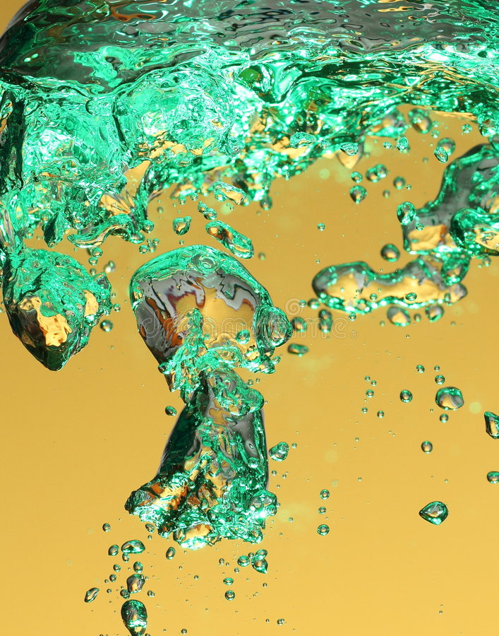 Green air bubbles in water. Macro view of green air bubbles in water shattering on yellowy background royalty free stock photography