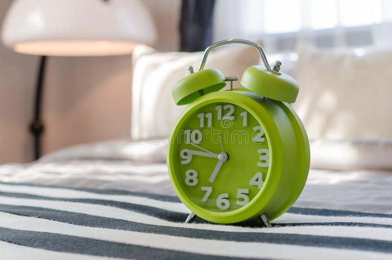 Green alarm clock on bed royalty free stock photos