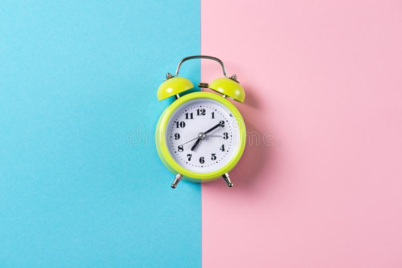 Green alarm clock with bells on blue and pink background, top view with copy space royalty free stock images