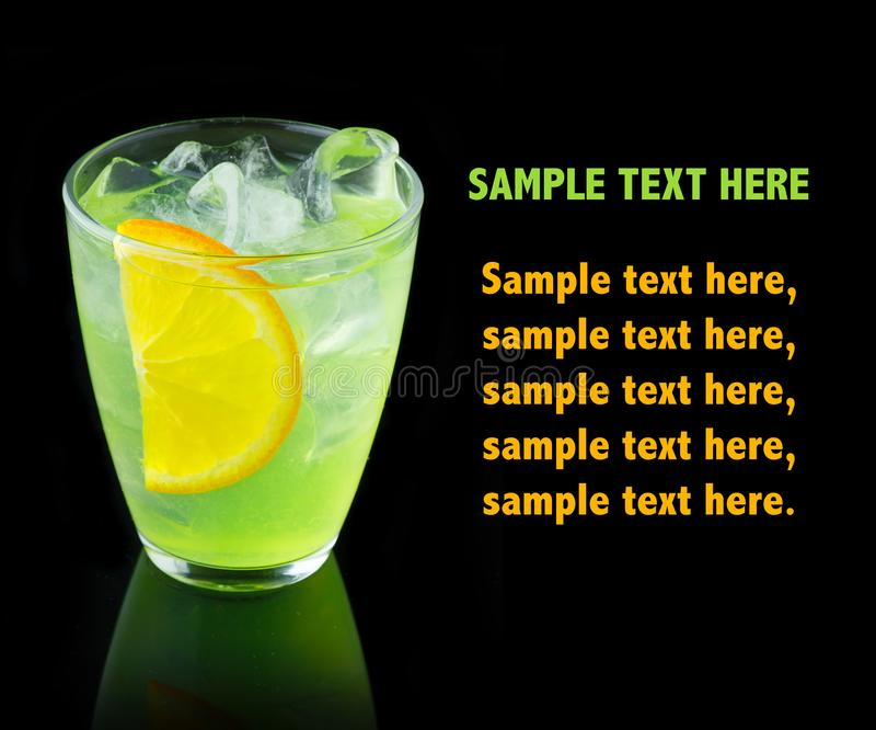 Green alcohol cocktail with lemon slice isolated on black stock photography
