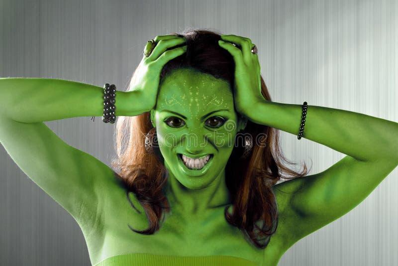 Green Alien Woman. A green alien or Martian woman posing over a silver brushed metal backdrop royalty free stock photos