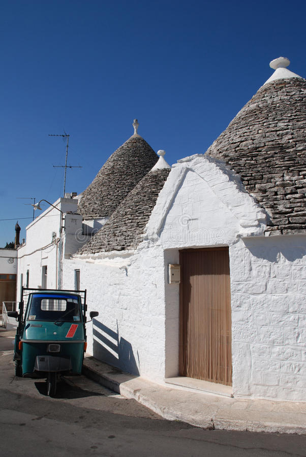 Green Ape Outside Trullo. An ape outside traditional trulli houses in Alberobello in Puglia, southern Italy. The trulli, which are protected under UNESCO World stock photography