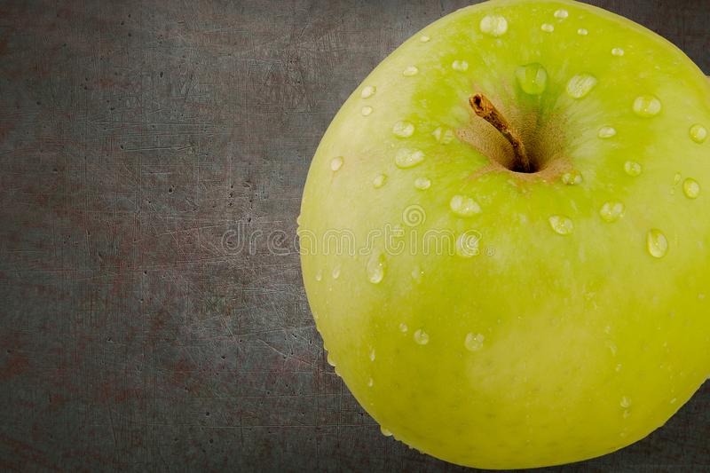 Green aple with water drops. Top view with copy space on dark background stock image