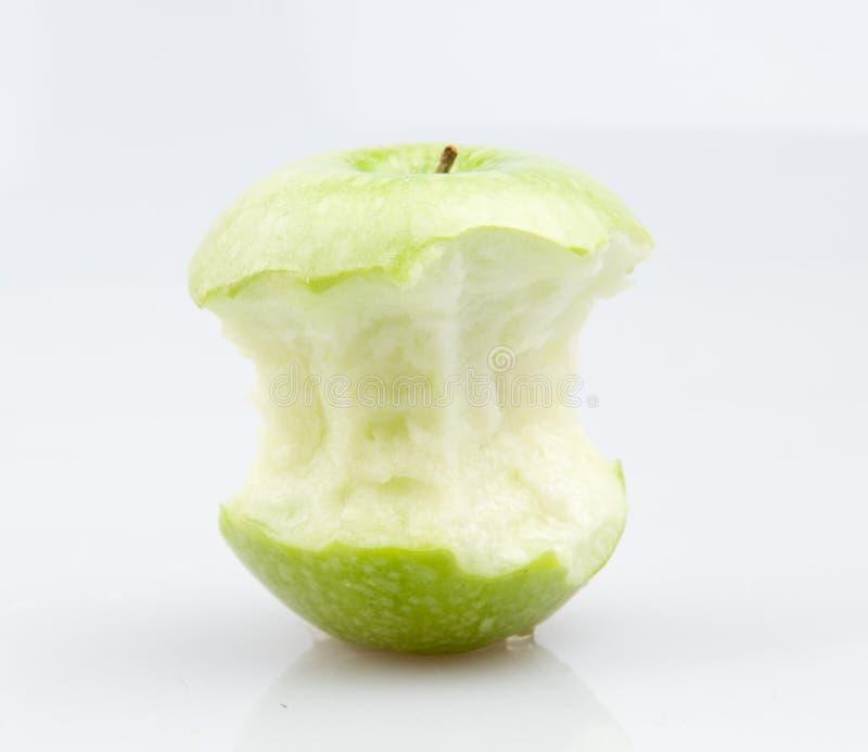 A green apple. A half eaten green apple stock photos