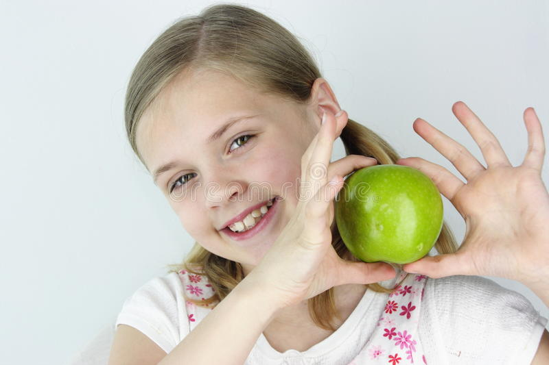 Green Apple. Young girl holding fresh green apple for healthy eating stock image