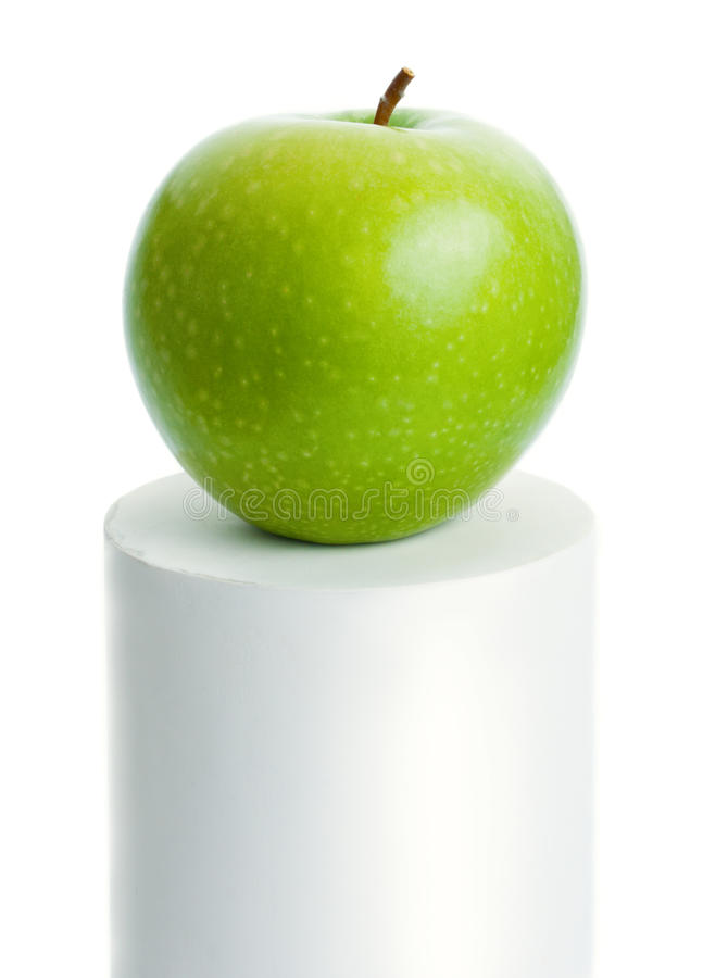 Green apple. Fresh ripe green apple placed on top of a white cylinder isolated on white background stock photos