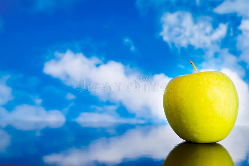 Green apple against blue sky. Display table with reflection for background stock photo
