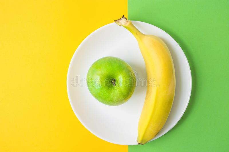 Green Apple Banana on White Plate on Contrast Background from Combination of Yellow and Green Colors. Vitamins Healthy Diet royalty free stock photo