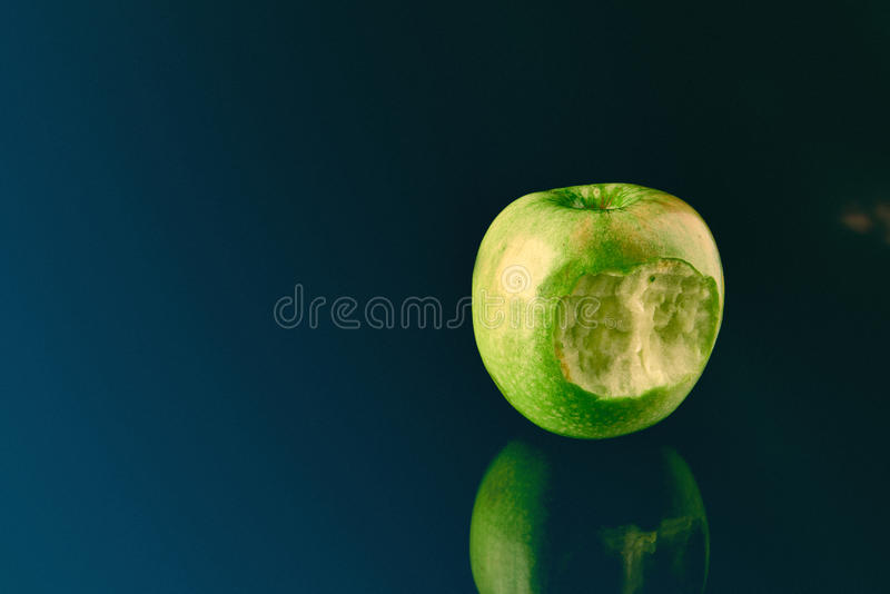 Green apple with big bite stock images