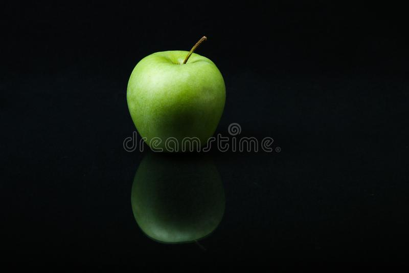 Green apple on a black background with reflection. royalty free stock images