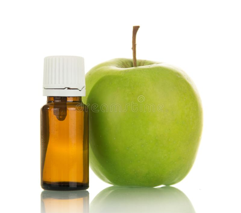 Green Apple and bottle of aromatic liquid for electronic Smoking, isolated on white royalty free stock image