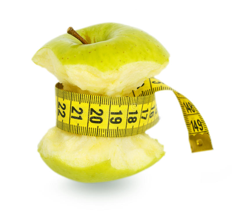 Green apple core and yellow measuring tape royalty free stock photography