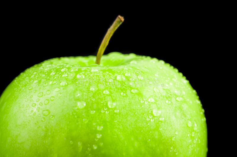 Green apple with droplets on black background stock photos