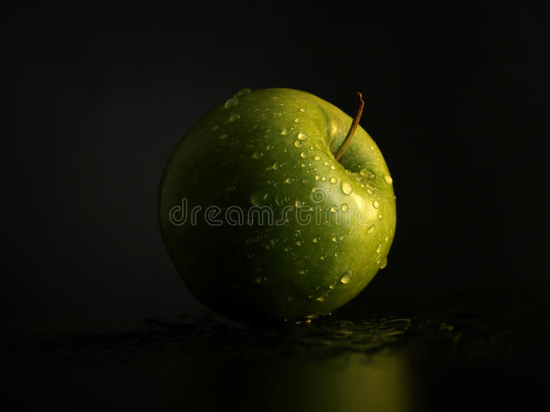 Green apple with drops of water royalty free stock image