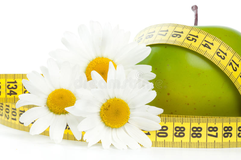 Green apple, flowers and measuring tape. royalty free stock images
