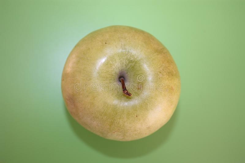 Green apple on a green background royalty free stock images