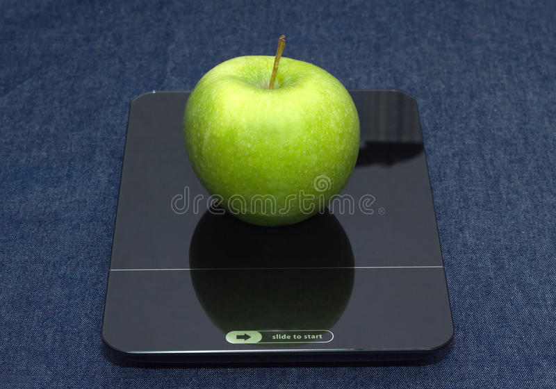 Green apple on kitchen scales closeup. Tasty green apple on kitchen scales over jeans background. Front view closeup royalty free stock photography